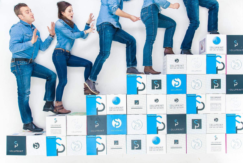 Photo team building par Amazing Studio. 5 personnesontent un escalier fait de boites en carton avec le logo de l'entreprise