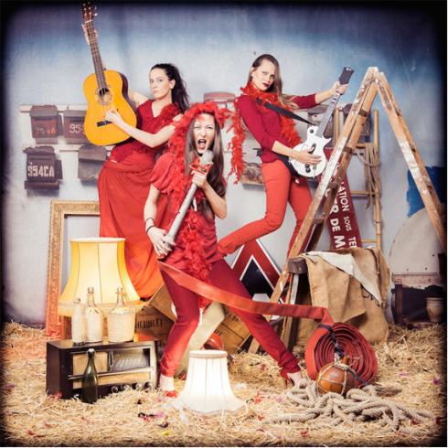 Plusieurs meilleures amies femmes mimant un groupe de musique karaoké déguisées en robe rouge dans une grange avec de la paille,  activité pour enterrement de célibataire fun et décalé. idées d'activités originale et insolites pour un enterrement