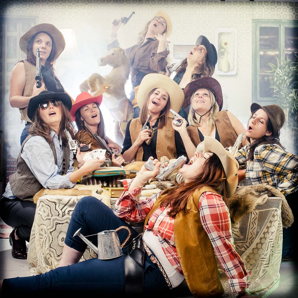 Un groupe de filles déguisées en cowboy très sexy autour d'une table. La scène se déroule dans un décor d'appartement vintage des années 80. elles organisent une surprise partie entre filles pour faire plaisir à la mariée. La scéne se déroule lors d'une séance shooting photo au studio le carré de Lyon