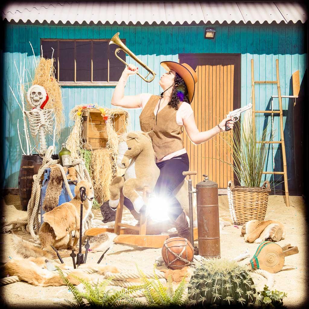 Femme sur son cheval, joliment déguisée en cowboy tout en jouant de la trompette sur la plage. Photo réalisée lors d'une séance de shooting pendant l'organisation d'une activité d'EVJF à Lyon