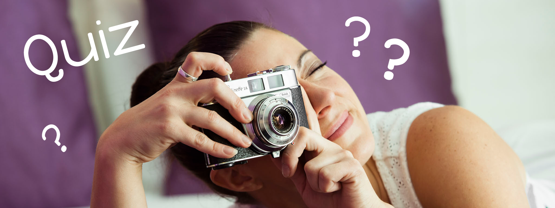 Femme qui souhaite apprendre la photo avec un jeu de quiz photo allongée sur son lit avec un appareil photo numérique dans les mains, question sur la photographie, test de connaissance photo, qcm photo numérique