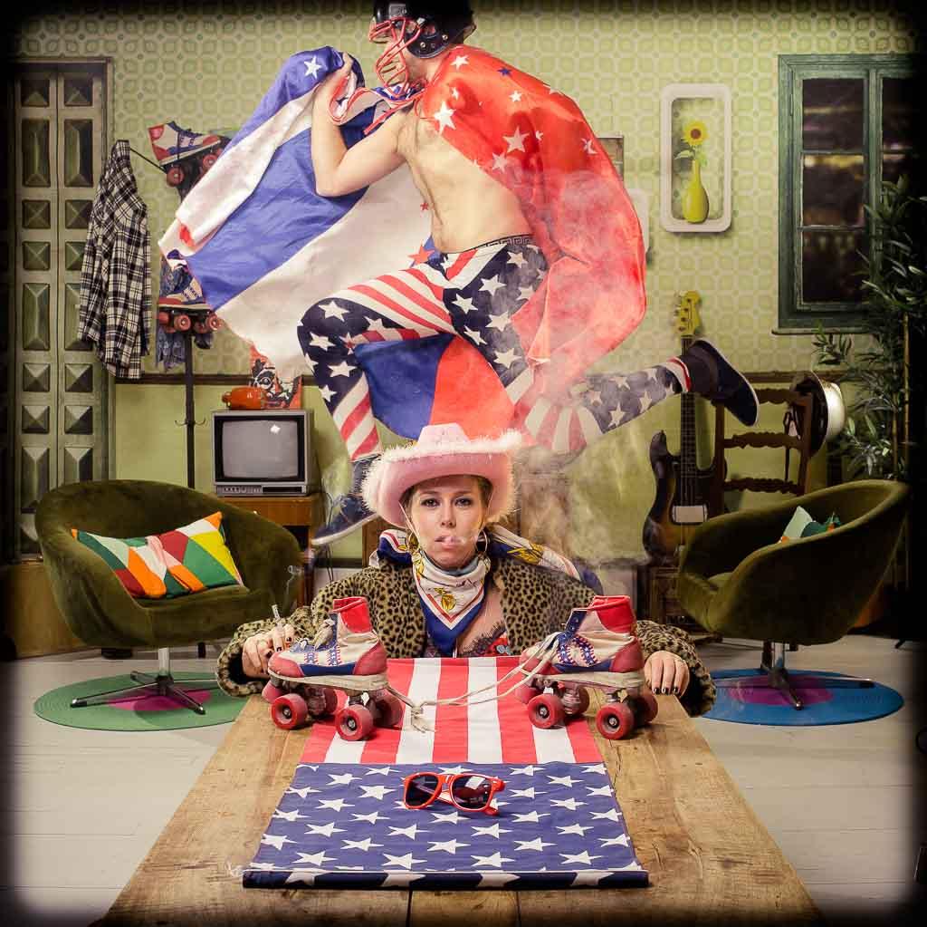 Une femme fume assise au premier plan autour d'une table sur laquelle est posé un drapeau américain. Des rollers sont également posés sur la table. Derrière elle son mari également déguisé en super héros américain saute au-dessus d'elle. Dans un décor vintage année 80 nous organisons des mise en scène pour des séance shooting photo. Photo réalisée lors d'une séance de shooting pendant l'organisation d'une activité d'EVJF à Lyon
