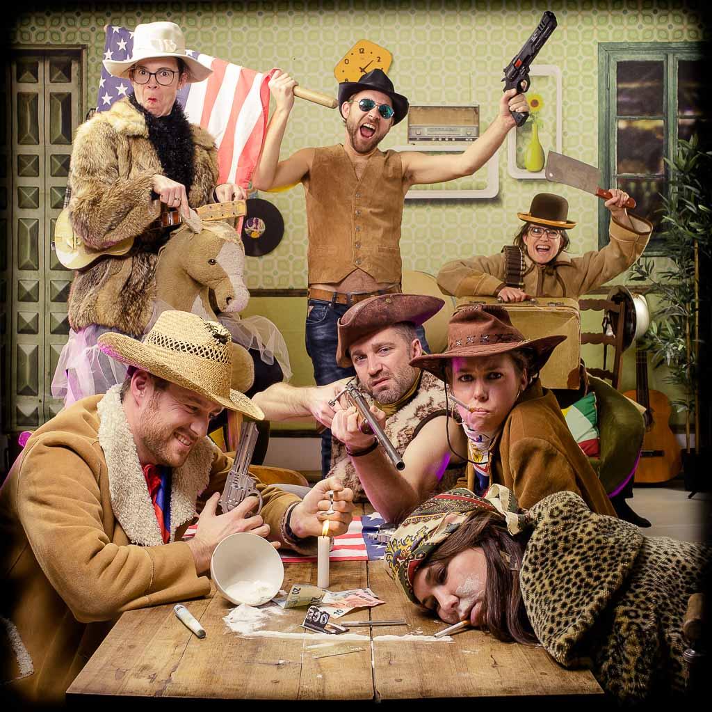 Groupe de copains et copines déguisés en cowboy avec un drapeau américain autour d'une table. Photo réalisée lors de l'organisation d'une activité d'EVJF à Lyon