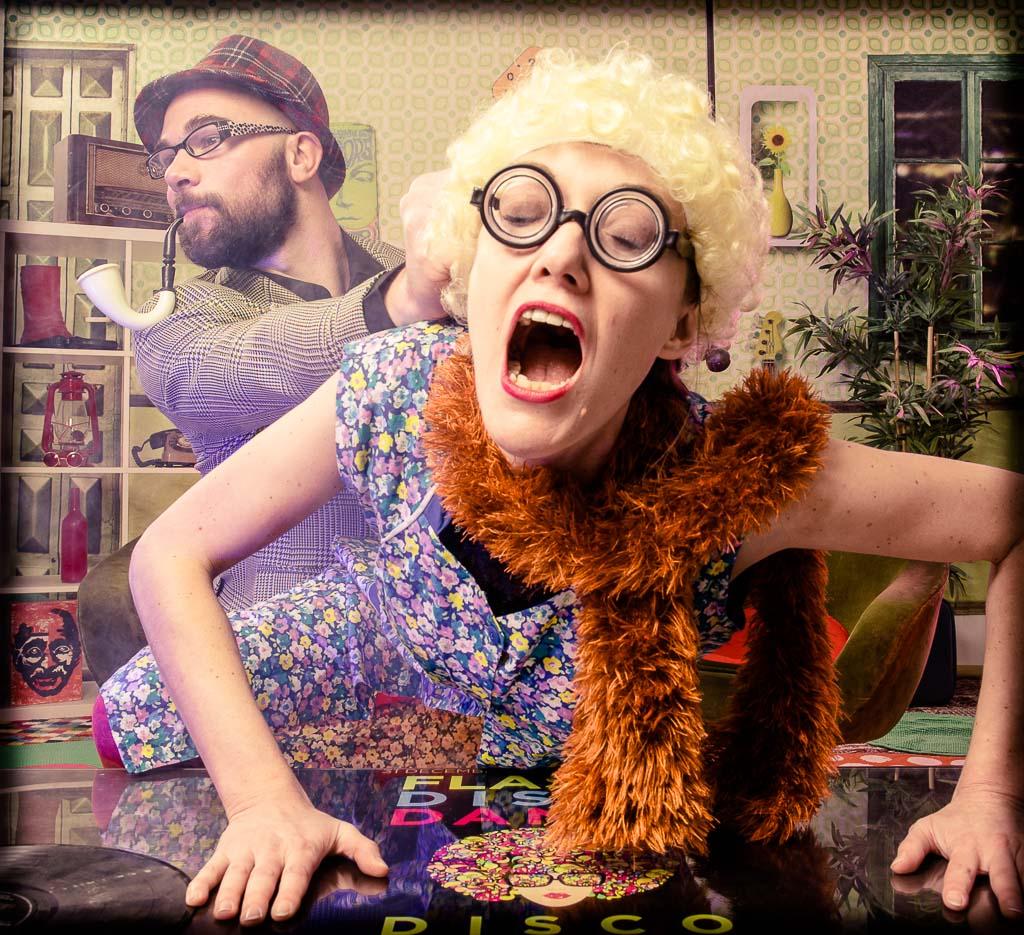 Une femme et un homme réalisant un gage sur une table dans un décor disco des années 70. Photo réalisée lors d'une séance de shooting pour une idée enterrement vie de jeune fille à Lyon
