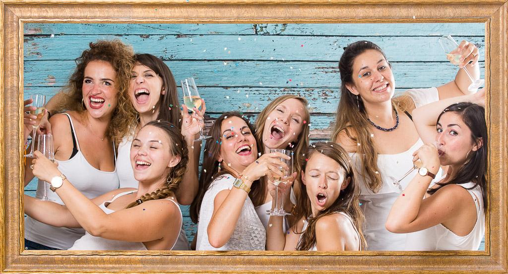 Un groupe de femmes faisant la fête entre amies avec un verre de champagne à la main pour un EVJF. Cette scène se déroule Lors de l'organisation d'une activité d'EVJF à Lyon au studio Le Carré