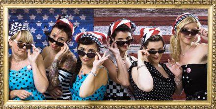 Groupe de femmes déguisées en tenues vintage année 50 américaine. Elles portes toutes des lunette de soleil afin de se protéger pour admirer leur copine qui va se marier. Mise en scène photographique sur décor dans un studio photo de Lyon idéol pour de groupe d'amies. Une séance photo fun et décalée en groupe jusqu'à 25 personnes dans le centre ville.